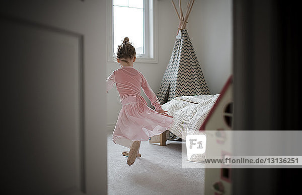 Rear view of girl in ballet costume dancing at home seen through doorway