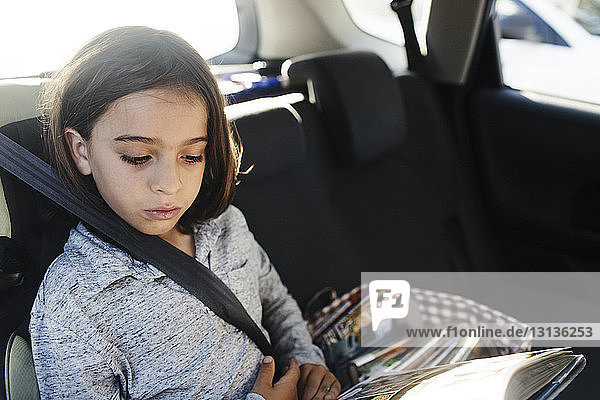 Schrägansicht eines ernsthaften Jungen  der im Auto sitzt und ein Buch liest