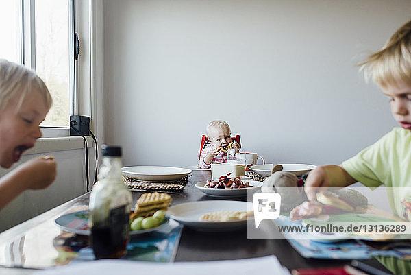 Geschwister beim Frühstück am Tisch