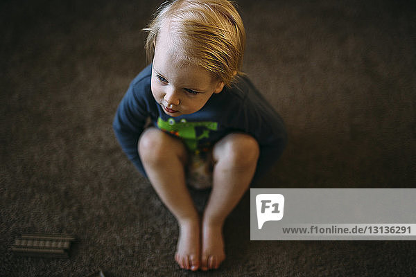 High angle view of boy sitting on floor at home