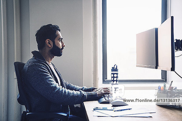 Side view of businessman using desktop computer while sitting at desk in office