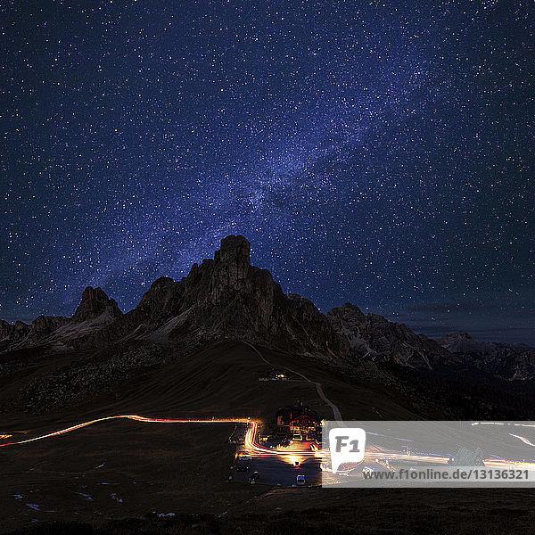 Landschaftliche Ansicht der Berge durch Lichtspuren gegen das nächtliche Sternenfeld