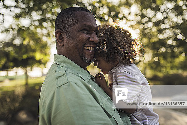 Happy father embracing son while standing against trees at park