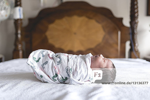 Side view of newborn baby girl wrapped in blanket Side view of newborn baby girl wrapped in blanket