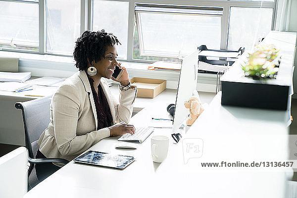 Geschäftsfrau  die mit einem Smartphone telefoniert  während sie im Büro einen Desktop-Computer benutzt