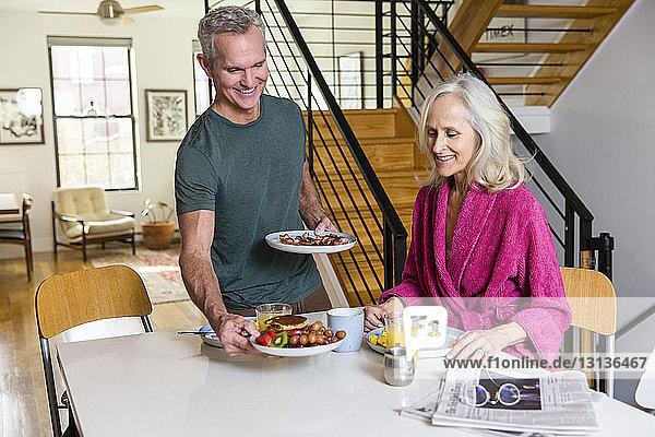 Mann deckt Teller auf dem Esstisch von Frau zu Hause