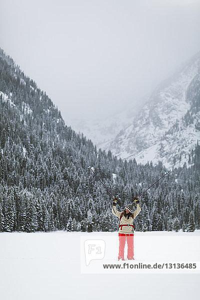 Frau mit Wanderstöcken steht auf schneebedecktem Feld