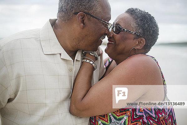 Glückliches älteres Ehepaar tanzt am Strand gegen bewölkten Himmel