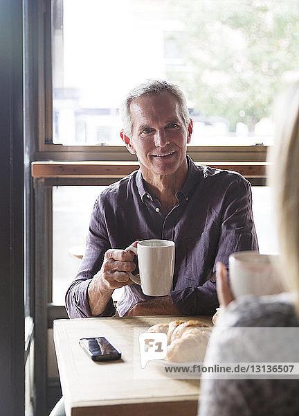 Reifer Mann unterhält sich mit Frau  während er im Café Kaffee gegen das Fenster trinkt