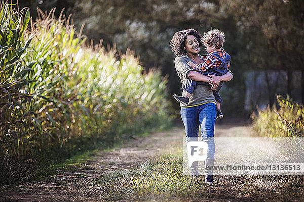 Mutter trägt Sohn beim Gehen auf dem Feld