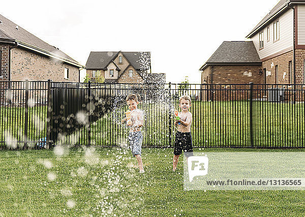 Portrait of boys squirting with water gun in backyard