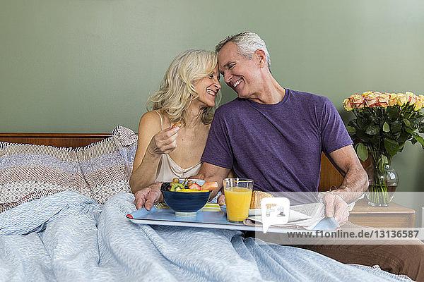 Glückliches Liebespaar mit Frühstück zu Hause auf dem Bett sitzend