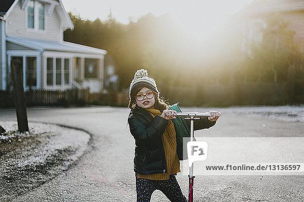 Porträt eines süßen Mädchens  das einen Roller auf dem Gehweg hält