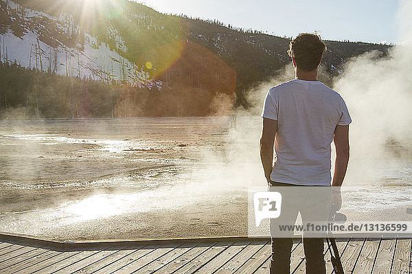 Rear view of hiker looking at steam coming out from hot spring at Yellowstone National Park