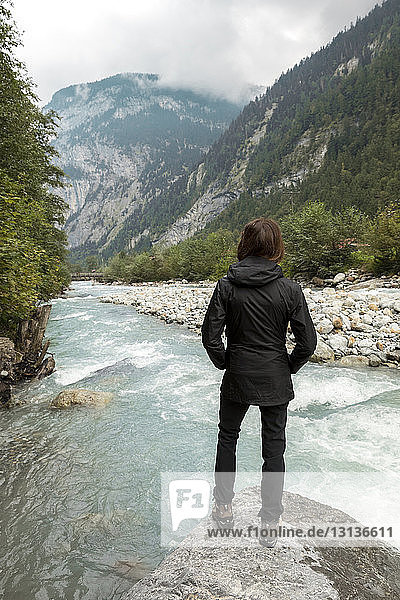Rückansicht einer Wanderin  die auf Felsen stehend auf Berge und Fluss schaut