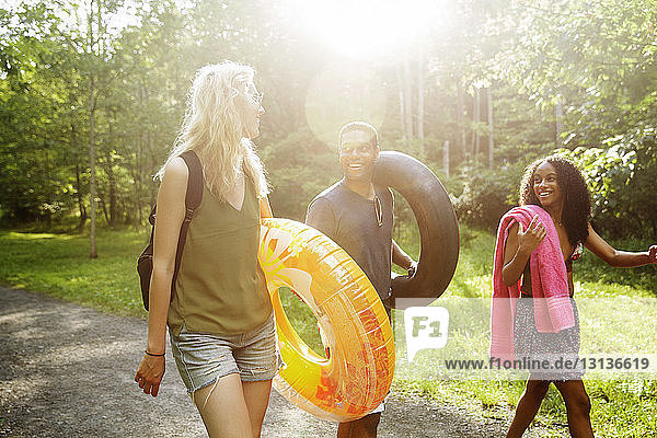 Cheerful friends carrying inflatable rings while walking on road in forest during summer