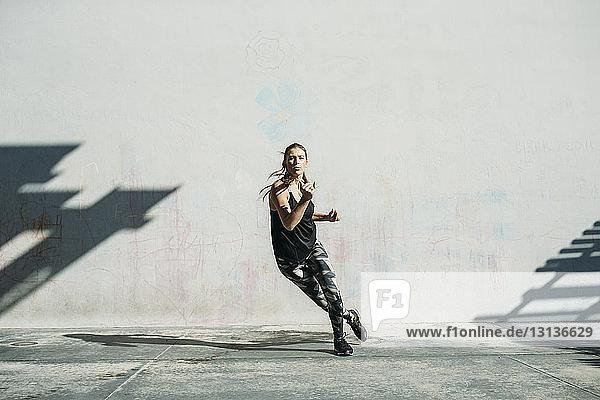 Determined female athlete exercising on sidewalk against white wall