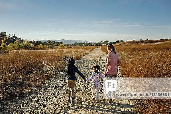 Rückansicht einer Mutter mit Töchtern  die auf einem Feldweg gegen den Himmel laufen