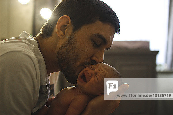 Father kissing newborn daughter while sitting at home Father kissing newborn daughter while sitting at home
