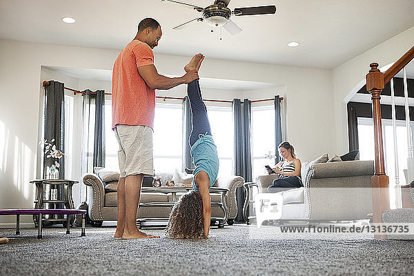 Father helping daughter doing handstand in living room at home