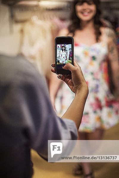 Ausschnitt einer handfotografierenden Frau in einer Boutique