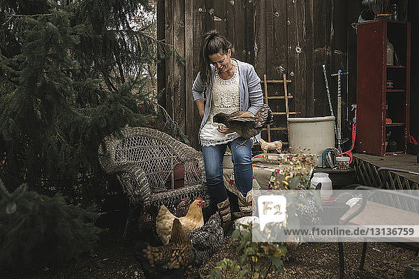 Smiling woman standing by hens in backyard