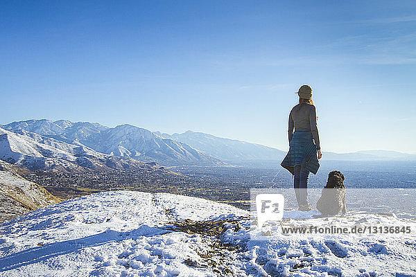 Rückansicht einer Frau mit Hund  die im Winter auf einem Berg gegen den Himmel steht
