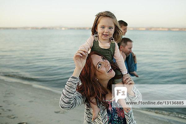 Fröhliche Eltern tragen Kinder auf Schultern am Strand vor klarem Himmel