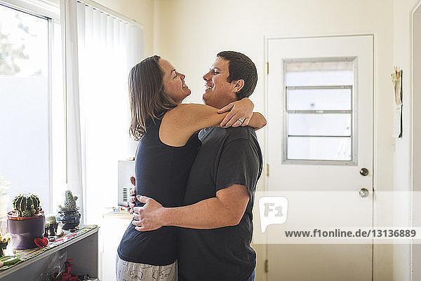 Seitenansicht eines glücklichen Paares  das sich zu Hause am Fenster umarmt