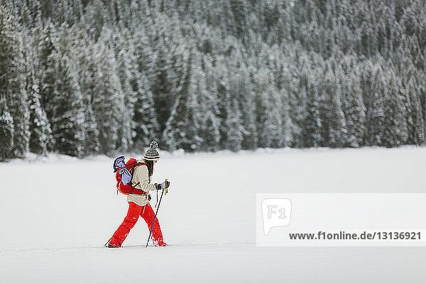 Seitenansicht einer Frau  die auf einem schneebedeckten Feld wandert