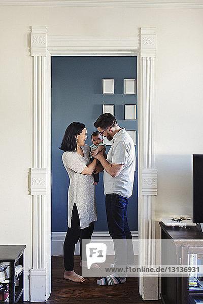 Vater spielt mit Tochter  die von Frau getragen wird  während er an der Tür steht