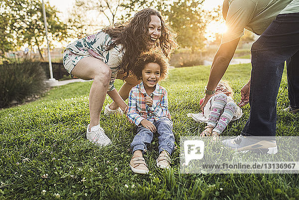 Parents playing with children on grassy field at park during sunset