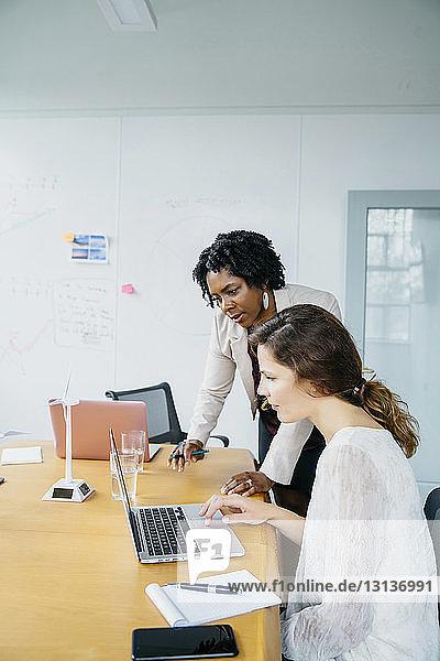 Weibliche Kollegen diskutieren über Laptop-Computer im Sitzungssaal im Büro