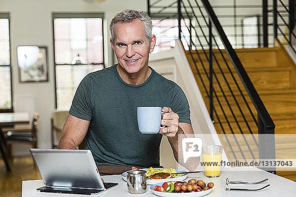 Porträt eines reifen Mannes  der eine Kaffeetasse hält  während er einen Tablet-Computer auf dem Esstisch zu Hause benutzt