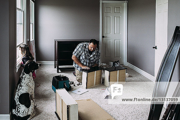 Father repairing drawers while daughter looking through window at home