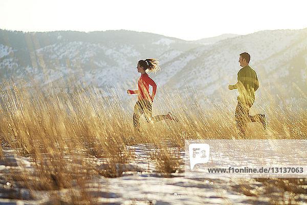 Paar läuft auf Feld gegen Berg
