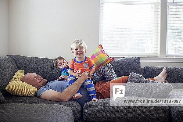 Vater genießt mit Söhnen  während er zu Hause auf dem Sofa liegt