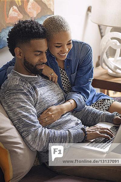 Ehepaar benutzt Laptop-Computer  während es zu Hause im Bett sitzt