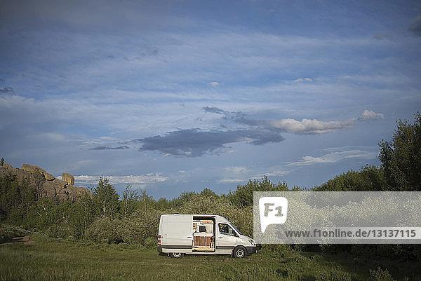 Wohnmobil auf Grasfeld vor bewölktem Himmel im Wald bei Sonnenschein geparkt
