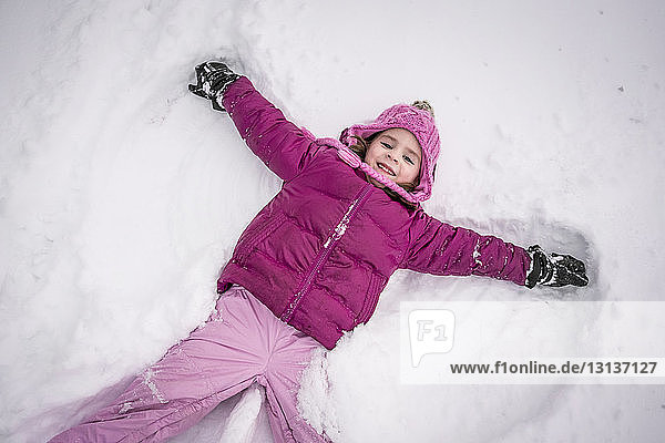 High angle portrait of happy girl making snow angel on field