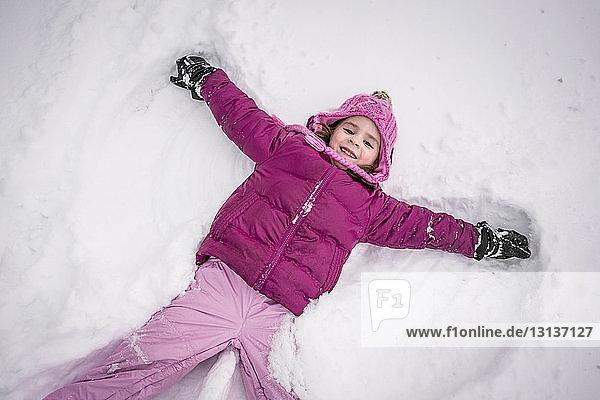 Hochwinkelporträt eines glücklichen Mädchens  das auf dem Feld einen Schneeengel macht