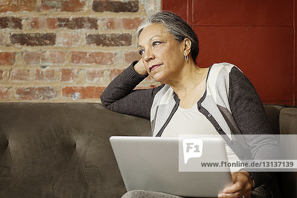 Woman with laptop computer looking away while sitting on sofa in office
