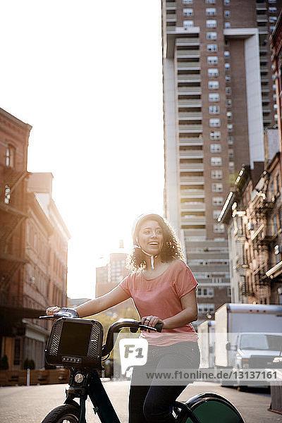Glückliche Geschäftsfrau sitzt auf dem Fahrrad in der Stadt