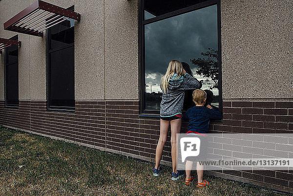 Rückansicht von Geschwistern  die durch ein Fenster spähen  während sie im Hinterhof stehen