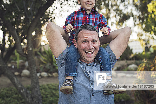 Portrait of cheerful father carrying son on shoulders while playing with him at park