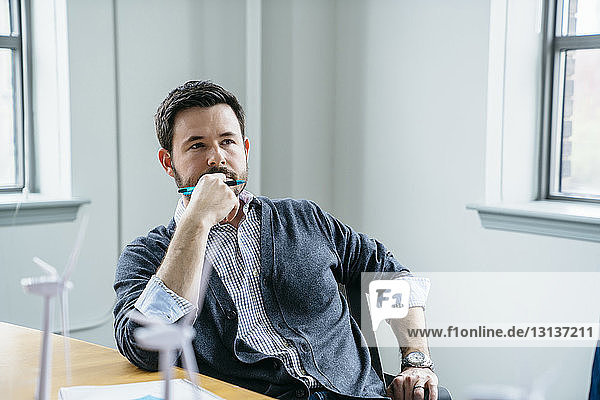 Thoughtful businessman sitting on chair in office