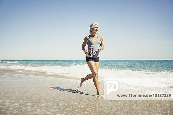 Full length of mature woman jogging on sea shore at Delray beach