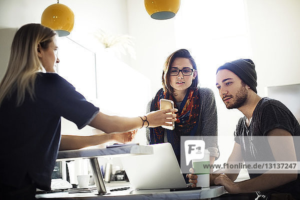 Woman showing smart phone to colleagues at cafeteria