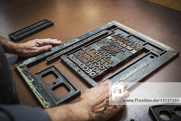 Man assembling letterpress on workbench in workshop