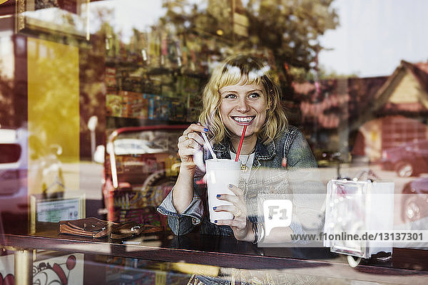 Happy woman looking away while holding milkshake glass in cafe